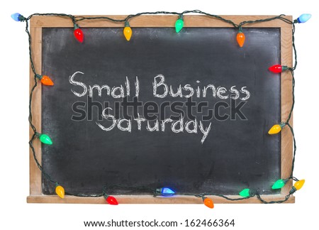 Small Business Saturday written in white chalk on a black chalkboard surrounded by festive colorful lights isolated on white - stock photo