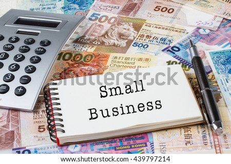 Small Business - Stack of Hong Kong dollar or banknotes with notepad and calculator conceptual - stock photo