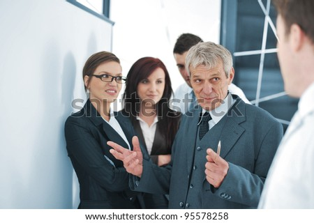 Small business team in the office in front of a whiteboard discussing a project - stock photo