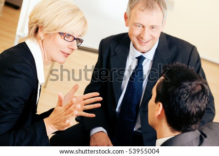 Small business team in the office in front of a whiteboard discussing a project very energetically - stock photo