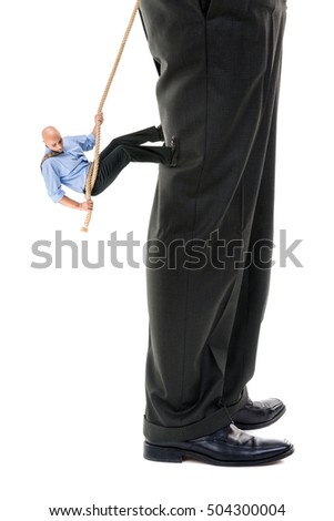 Small businessman climbing big business player's leg