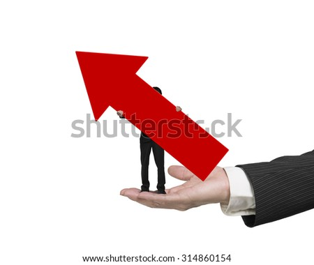 Small businessman holding red arrow up sign, standing on big male hand palm open, with sunny sky cityscape background.