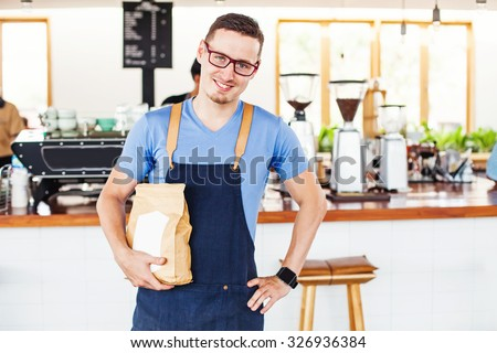 small cafe owner holding a package of coffee beans in front of the bar