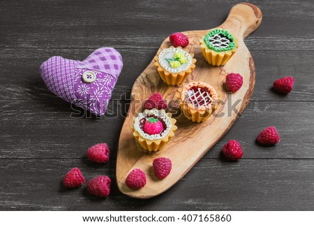 Small cakes petit fours in the form of baskets with cream and jam on a wooden plank from a tree of olive, heart cloth, worn on a dark black background in rustic style - stock photo