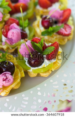 Small cakes with different stuffing. Cupcakes with fruits. Cake with icing and fresh berry. - stock photo