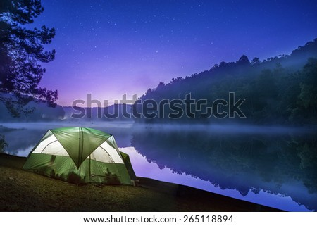 Small Camping Tent Illuminated Inside at early morning light with the shadow of the mountain and reflection on the water at Pang Ung Forestry Plantations,Maehongson, North of Thailand - stock photo