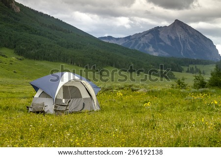 Small camping tent with chairs setup in mountain meadow filled with wildflowers with high mountain peak in distance - stock photo