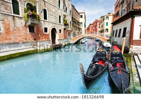 Small canal in the Venice, Italy with bridge over it on Calle Zancani and two Venetian gondolas - stock photo