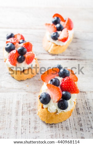 Small canape, crostini with grilled baguette with cream cheese, blueberry, strawberry and mint on old white wooden background. Delicious appetizer or dessert. - stock photo