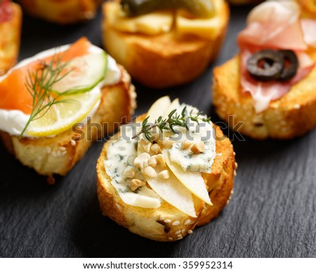Small canape, crostini  with grilled baguette with the addition of blue cheese,apple slices, cashew nuts and fresh thyme on black background. Delicious appetizer - stock photo