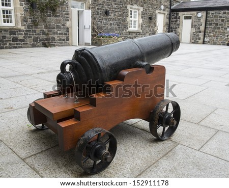 small cannon sitting in a large courtyard - stock photo