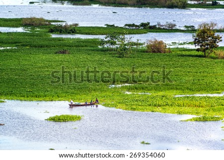 Small canoe in the Itaya River near Iquitos, Peru in the Amazon rainforest - stock photo