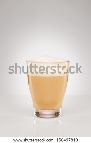 small cappuccino in a glass cup on gray background - stock photo