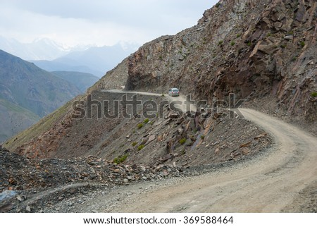 Small car on the steep and shallow dangerous mountain road - stock photo
