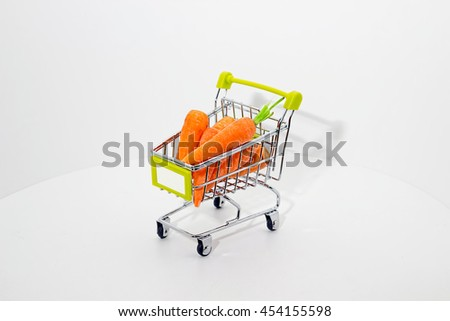 Small carrots in a little shopping cart. White background. Eco food.