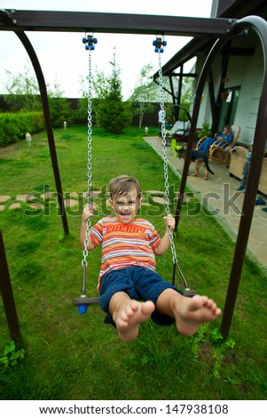 Small caucasian boy has fun at swing outdoor
