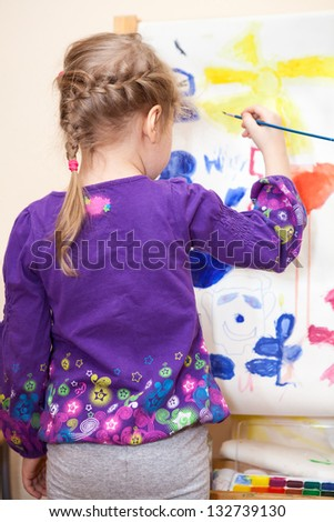 Small Caucasian child painting with brush and paint