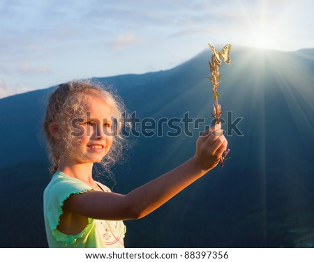 Small  caucasian girl in last mountain sunset light admire on yellow Swallowtail butterfly - stock photo