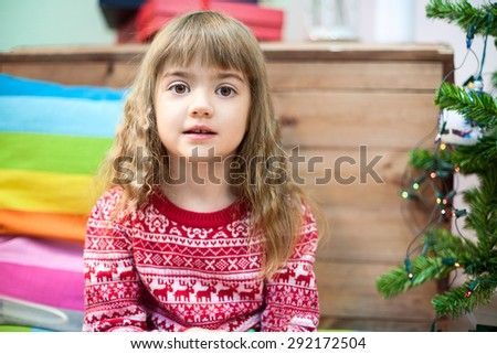 Small Caucasian girl portrait in sweater, sitting on the floor near Christmas tree - stock photo