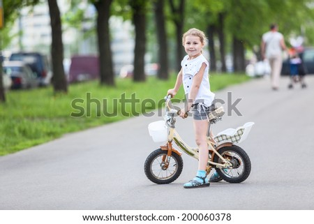 Small Caucasian girl riding a bicycle - stock photo