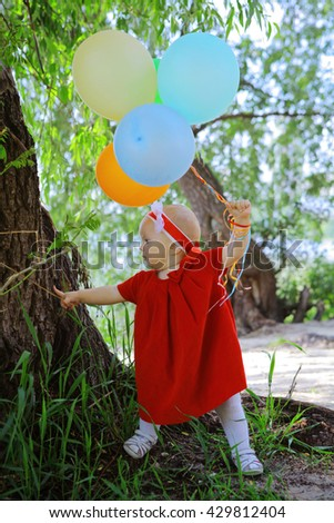 Small caucasian plays ner the tree with colorful balloons. Portrait of cute adorable baby girl in red dress celebrating her first birthday in the wood with balloons looking away from camera - stock photo