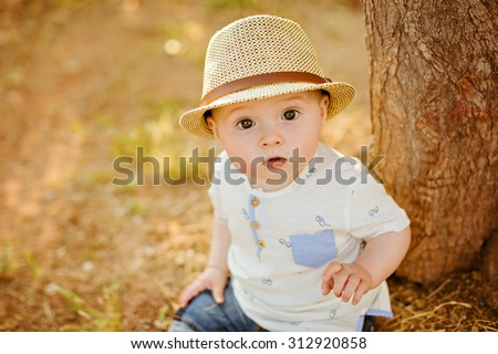 Small charming and very beautiful baby boy with big brown eyes in a hat sits near a tree on the grass at sunset in the summer, close-up - stock photo