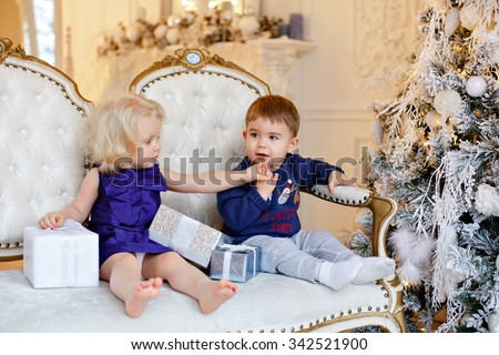 Small charming baby boy in a blue sweater and a little blond girl sitting in a chair against a background of Christmas lights and holding hands in the interior of the house - stock photo