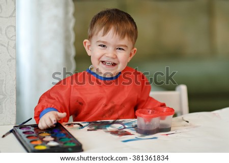 Small charming baby boy in a red robe draws colored paint sitting at the table and smiling at home