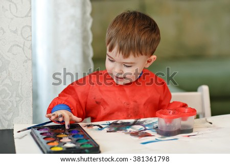 Small charming baby boy in a red robe draws colored paint sitting at the table at home