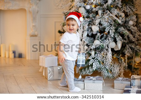 Small charming baby boy in Santa hat and light-colored clothing costs about Christmas trees with gifts and smiles, in the interiors of the house - stock photo