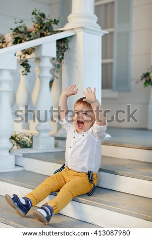 Small charming boy sits on the stairs and shouted, raising his arms up, rejoices and laughs, against the background of the house - stock photo