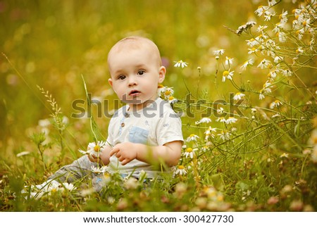 Small charming toddler boy light t-shirt sits in a field with daisies in the summer and stares up