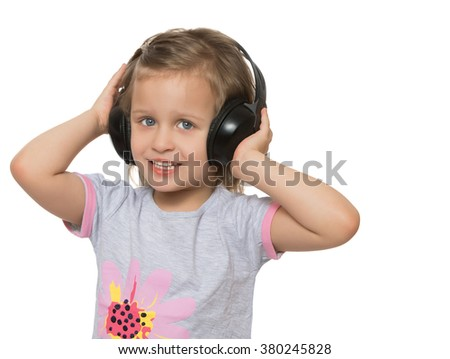 Small, cheerful girl pulls hands to the head stereo headphones large. Girl listens to music. Closeup - Isolated on white background - stock photo
