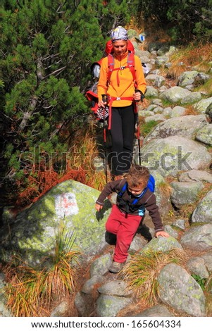 Small child and his mother descending the mountain trail - stock photo