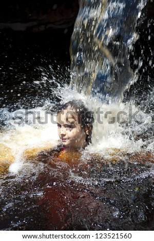 Small child bathing in a waterfall