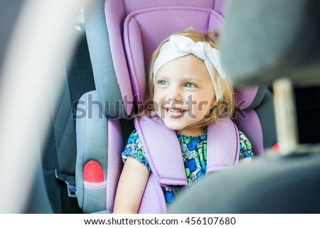 small child (blonde girl) 4 years in car seat wearing seat belts happy is going to go in the path of the road
