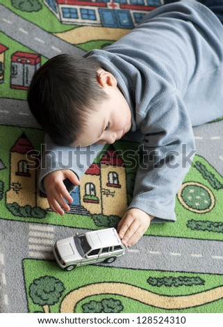 Small child boy playing on a road themed carpet with a toy car.. - stock photo