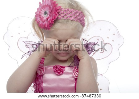 Small child dressed as a fairy, has sad expression and is rubbing her eyes