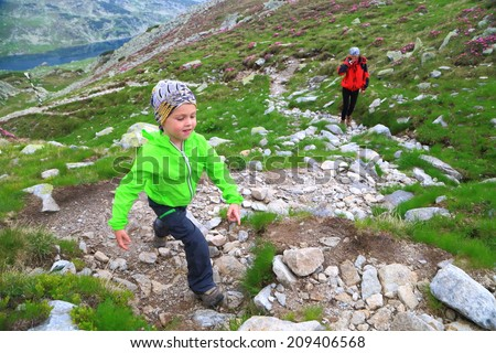 Small child followed by his mother on the mountain trail - stock photo