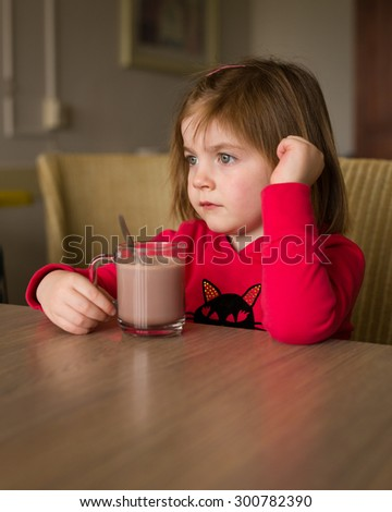 Small child girl looking sad while holding a cup of hot chocolate. - stock photo