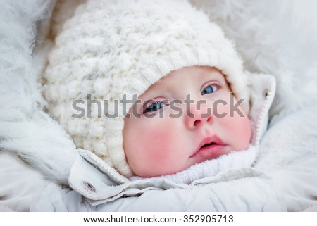 small child in a knitted cap in winter with hoarfrost on the eyelashes