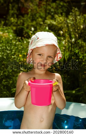 Small child in Panama in an inflatable pool with pink bucket of water. - stock photo