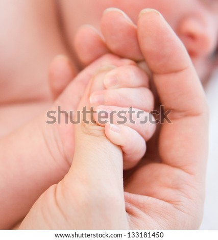 small child is held by the hand the parent - stock photo