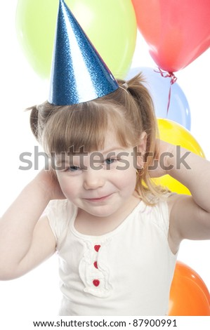 small child is putting a party hat string around the back of her head