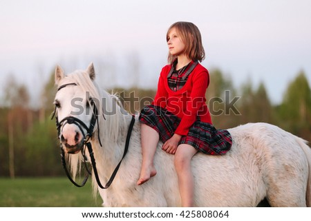 Small child is sitting in white pony thought and looking up Outdoors - stock photo