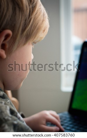 Small child looking at a gambling website - stock photo
