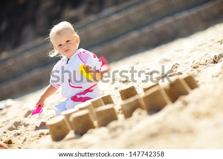 small child making pies from the sand - stock photo