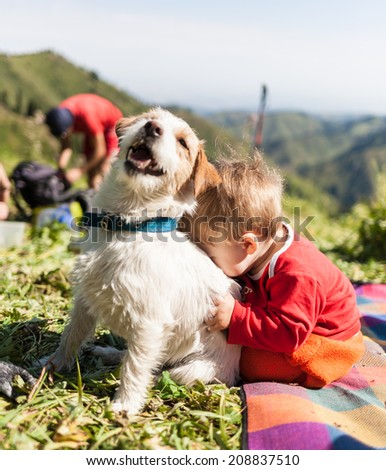 small child playing with a dog on the nature - stock photo