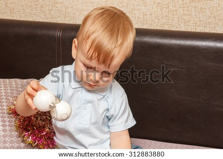 small child playing with Christmas balls sitting on the couch