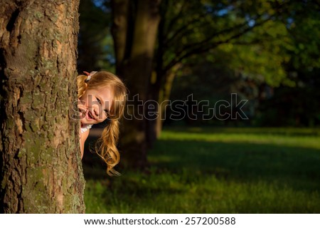 small child plays Spring Park, hiding behind a tree - stock photo